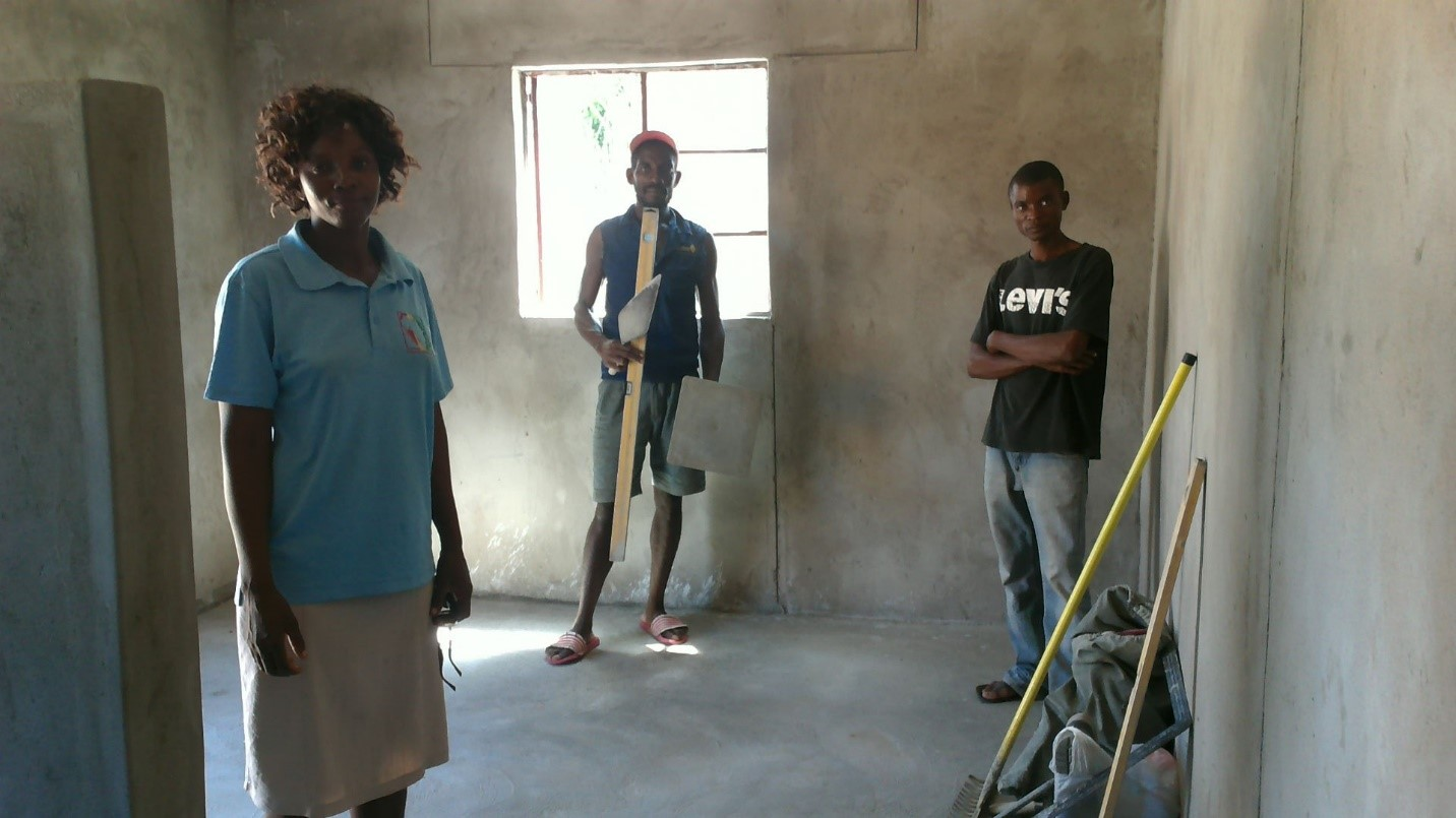 Workers clean the inside of the newly constructed home.